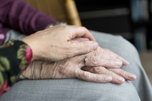 Woman holding elderly mother's hand